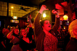 "The caption read: ""Front to back, Alex Hudson, Hanna Brooks Olsen and Sarah Anne Lloyd cheer during the Yes for Seattle Transit Election Night party at the Comet Tavern in Capitol Hill."""